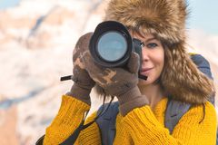 Portrait of a sweet tourist girl in a big fur hat takes pictures on her digital camera in the mountains. Portrait of a sweet tourist girl in a big fur hat takes Stock Photography