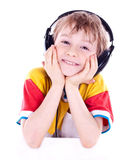 Portrait of a sweet young boy listening to music. On headphones against white background Royalty Free Stock Photos