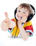 Portrait of a sweet young boy listening to music. On headphones against white background Royalty Free Stock Images