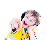 Portrait of a sweet young boy listening to music. On headphones against white background Royalty Free Stock Photo