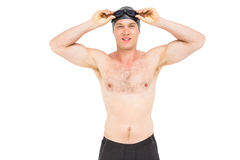 Portrait of swimmer holding swimming goggles. Portrait of swimmer looking down and holding swimming goggles on white background royalty free stock images