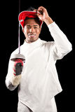 Portrait of swordsman standing with fencing mask and sword. On black background Stock Photography