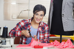 Portrait Of Tailor Cutting Fabric At Workbench. Portrait of happy female tailor cutting fabric at workbench by mannequin in sewing factory Stock Images