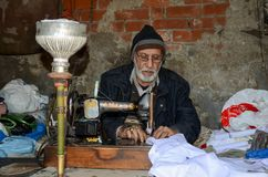Portrait of a Tailor in the Famous Food Street, Lahore, Pakistan. Portrait of an old Tailor working hard in the Famous Food Street of Lahore, Pakistan Stock Image