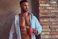 Portrait of a tall bearded male with a muscular body. Portrait of a tall bearded male with a muscular body, standing against a wall near the window, drink a cup Stock Images