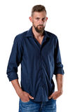 Portrait of tall young man with beard in blue shirt and jeans Stock Images