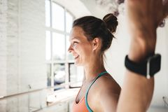 Portrait of tanned healthy woman doing fitness exercises in sunny gym royalty free stock photography