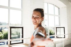 Portrait of tanned healthy woman doing fitness exercises in sunny gym stock photo