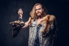 Portrait of a tattoed redhead hipster male with long luxuriant hair and full beard dressed in a t-shirt and jacket holds. A keeps the scarecrow of an owl and stock photo
