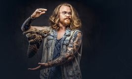 Portrait of a tattoed redhead hipster male with long luxuriant hair and full beard dressed in a t-shirt and jacket holds. A keeps the scarecrow of an owl in a stock photo