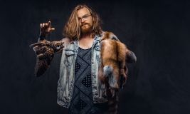 Portrait of a tattoed redhead hipster male with long luxuriant hair and full beard dressed in a t-shirt and jacket holds. A keeps the scarecrow of an owl and royalty free stock images