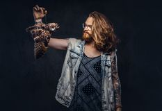 Portrait of a tattoed redhead hipster male with long luxuriant hair and full beard dressed in a t-shirt and jacket holds. A keeps the scarecrow of an owl in a stock photos