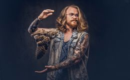 Portrait of a tattoed redhead hipster male with long luxuriant hair and full beard dressed in a t-shirt and jacket holds stock photo