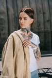 Portrait of tattooed woman with jacket on shoulder. Looking away royalty free stock photos