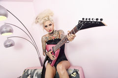 Portrait of a tattooed woman wearing corset while holding guitar against wall. Portrait of a tattooed women wearing corset while holding guitar against wall stock photos