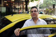 Portrait of a taxi driver with cab. Portrait of a taxi driver with his yellow cab Stock Image
