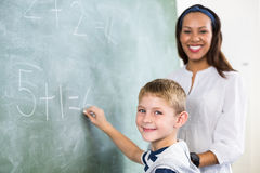 Portrait of teacher assisting boy in doing addition on chalkboard. Portrait of teacher assisting boy doing addition on chalkboard in classroom stock images