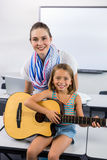 Portrait of teacher assisting girl to play guitar in classroom Stock Images