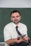 Portrait of  teacher at the blackboard. Portrait of  teacher or professor, standing, smiling against green blackboard, holding tablet Stock Photos