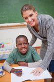Portrait of a teacher explaining something to a smiling schoolbo Royalty Free Stock Photo
