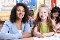 Portrait Of Teacher With Female Elementary School Pupil In Class. Teacher With Female Elementary School Pupil In Class Stock Image