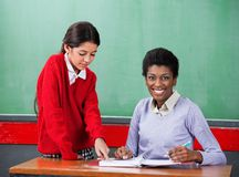 Portrait Of Teacher With Girl Pointing On Binder Stock Images