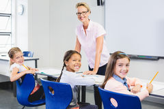 Portrait of teacher and kids in classroom. At school Stock Photography