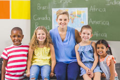 Portrait of teacher and kids in classroom. At school Stock Image