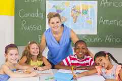 Portrait of teacher and kids in classroom. At school Royalty Free Stock Photography