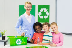 Portrait of teacher and kids standing in classroom. With recycle logo Stock Image