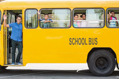 Portrait of teacher and kids waving hand from bus Stock Photo