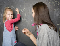 Portrait of teacher and little student, mother and daughter near blackboard Royalty Free Stock Photo
