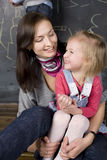 Portrait of teacher and little student, mother and daughter near blackboard Royalty Free Stock Image
