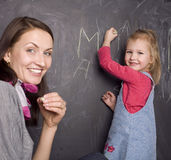 Portrait of teacher and little student, mother and daughter near blackboard Royalty Free Stock Images