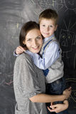 Portrait of teacher and little student, mother and daughter near blackboard Stock Photo