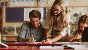 Teacher helping student during her class Stock Photography