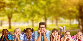Composite image of portrait of teacher lying down with students royalty free stock image