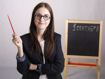 Portrait of the teacher, with a pointer and a Board in the background Royalty Free Stock Photo