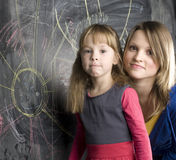 Portrait of teacher with pupil at blackboard. Young family Royalty Free Stock Images