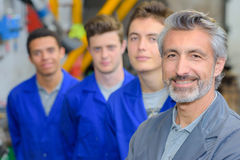 Portrait of teacher stood in front of his three apprentices Stock Images