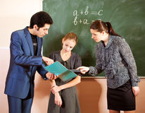 Portrait of a teachers explaining something to a smiling schoolbo. Portrait of a teaches scolding girl in a classroom Stock Images