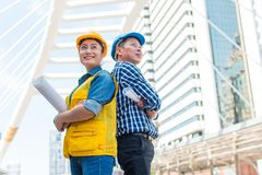 Portrait of team partners industrial engineer standing and looking to camera wear safety helmet with holding inspection on. Building outside. Engineering tools royalty free stock images