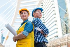 Portrait of team partners industrial engineer standing and looking to camera wear safety helmet. With holding inspection on building outside. Engineering tools stock image