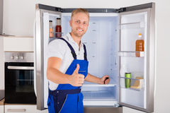 Portrait Of Technician Gesturing Thumbs Up. In Front Of Refrigerator Stock Photo