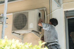 Portrait of technician in hardhat connecting outdoor air conditioning. Unit Stock Photos