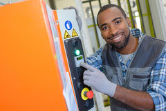 Portrait technician pointing to panel on machine in factory royalty free stock image