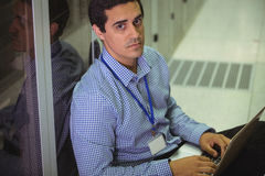 Portrait of technician using laptop. In server room Royalty Free Stock Photography