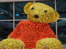 Portrait of Teddy Bear during Dubai Shopping Festival. Yellow Teddy Bear in red plover sitting on floor inside Festival Mall during Dubai Shopping Festival Stock Images
