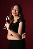 Portrait of teen in black dress with wine. Close up. Dark red background Royalty Free Stock Photos