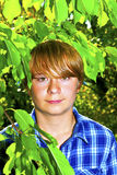 Portrait of a teen boy with blonde hair standing in the garden Royalty Free Stock Photo